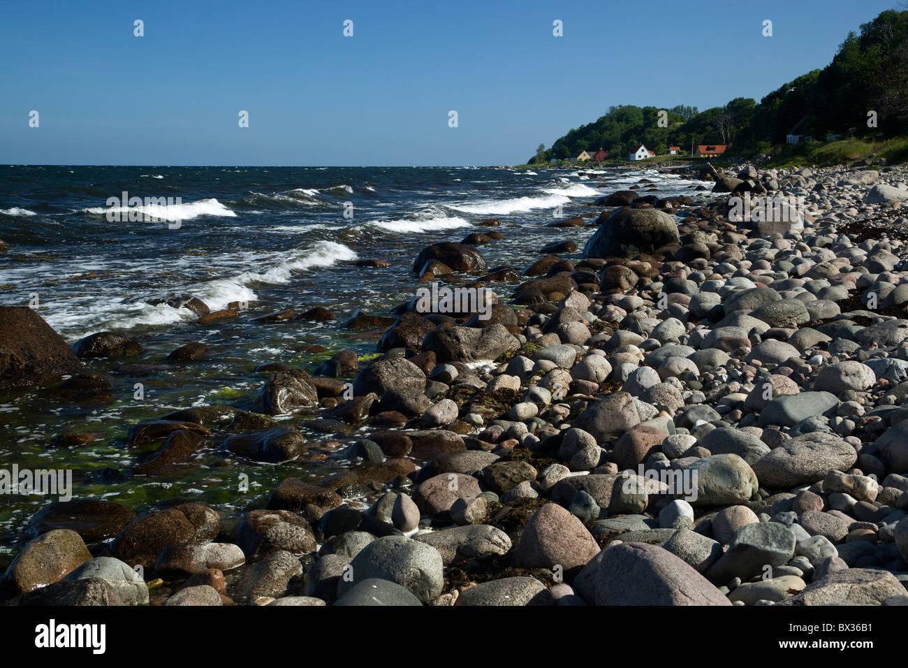 Stony Shore. Bornholm. Denmark. In the background the little fishing village, Helligpeder (Holypeter). Stock Photo