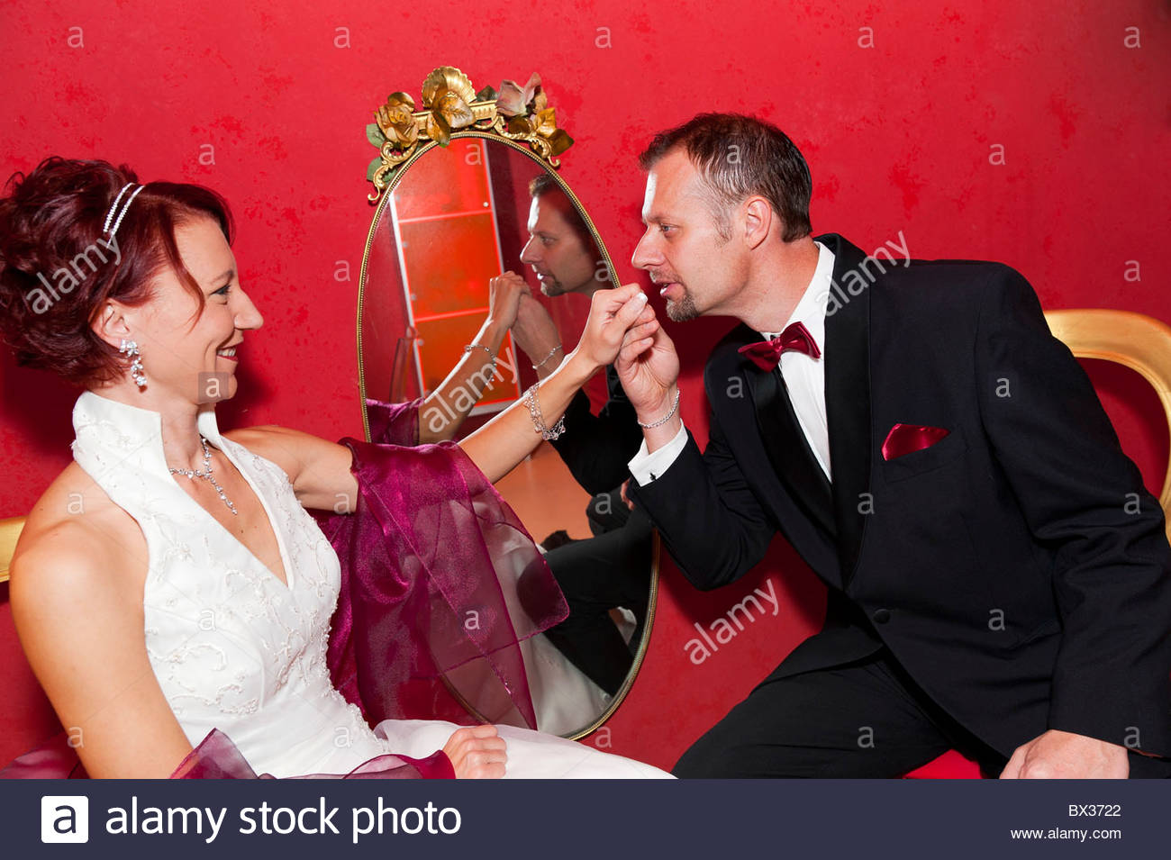 Groom gallantly kissing bride's hand - Stock Image