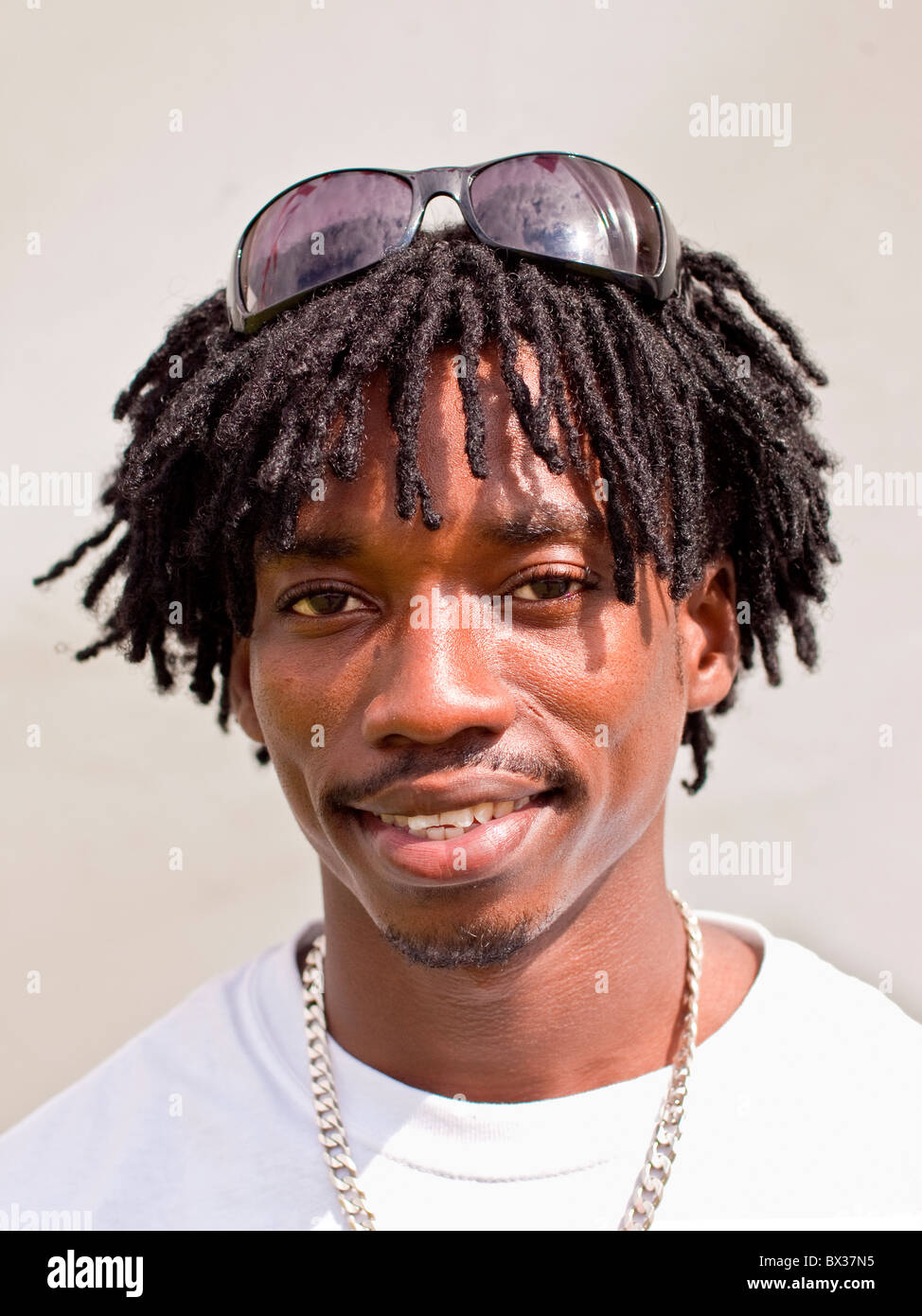Black male Afro-Caribbean coloured background sun glasses good looking lively attractive handsome smile healthy - Stock Image
