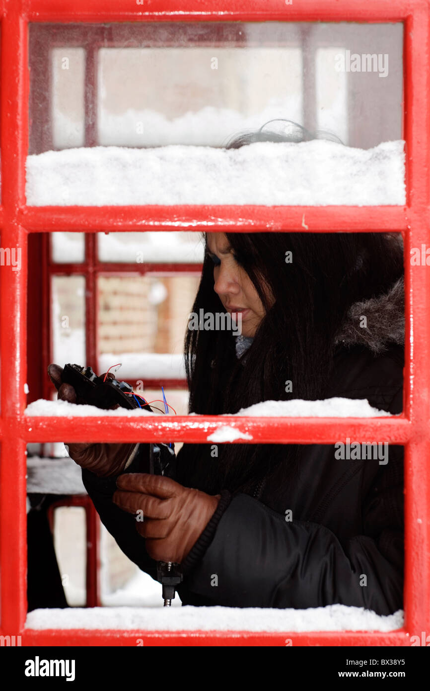 woman in snow covered telephone box looking at vandalized handset - Stock Image