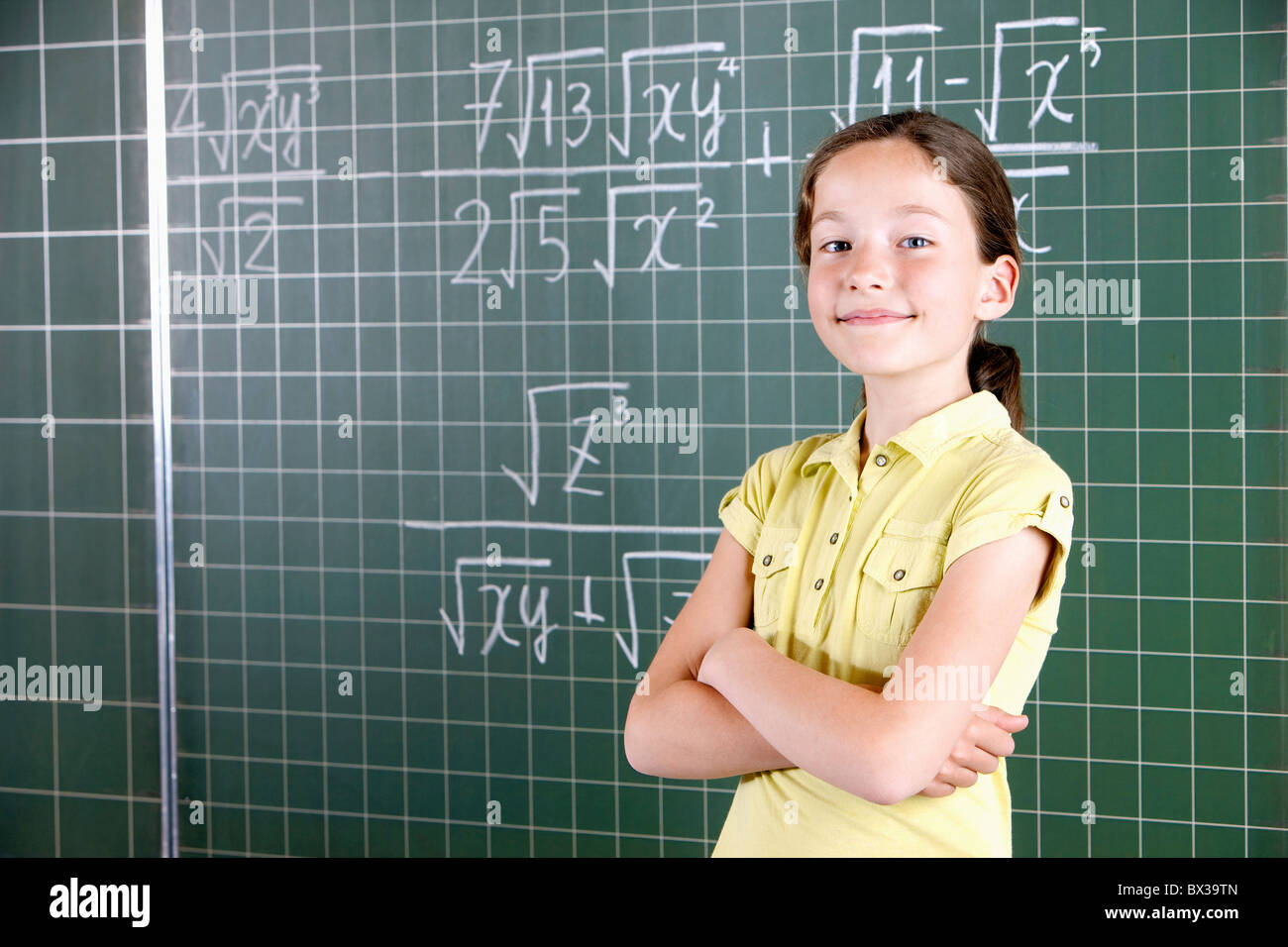 young girl in front of blackboard in classroom - Stock Image