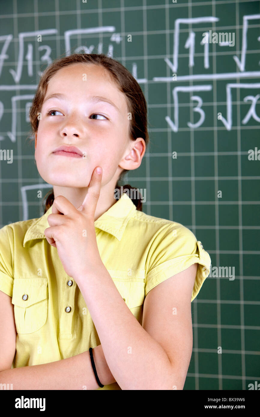 young girl in front of blackboard thinking - Stock Image