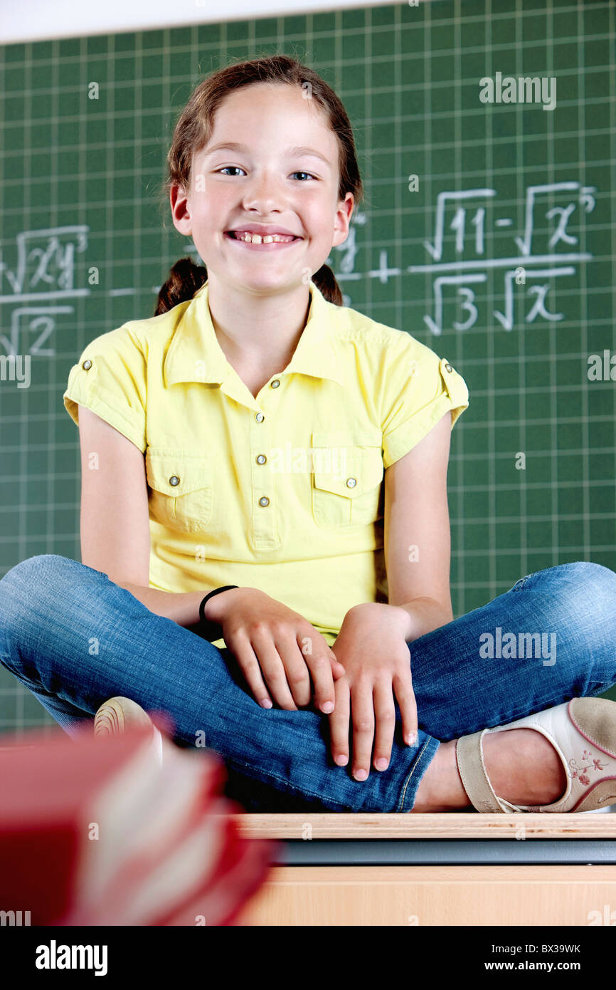 young girl sitting on desk in front of blackboard - Stock Image