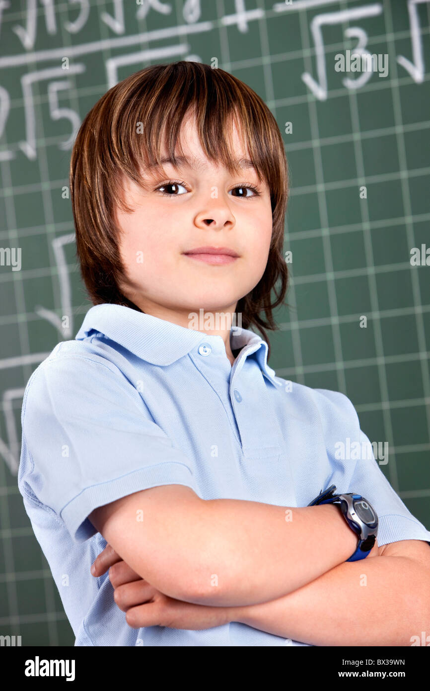 portrait of young boy in classroom in front of blackboard - Stock Image