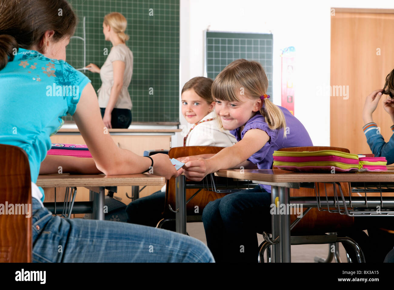 young girl giving little note to friend in classroom - Stock Image
