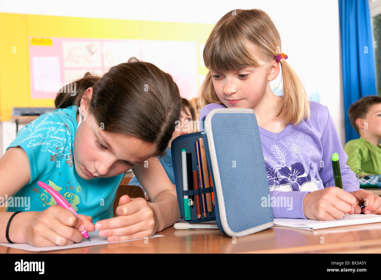 two young girls writing test in classroom one trying to cheat - Stock Image