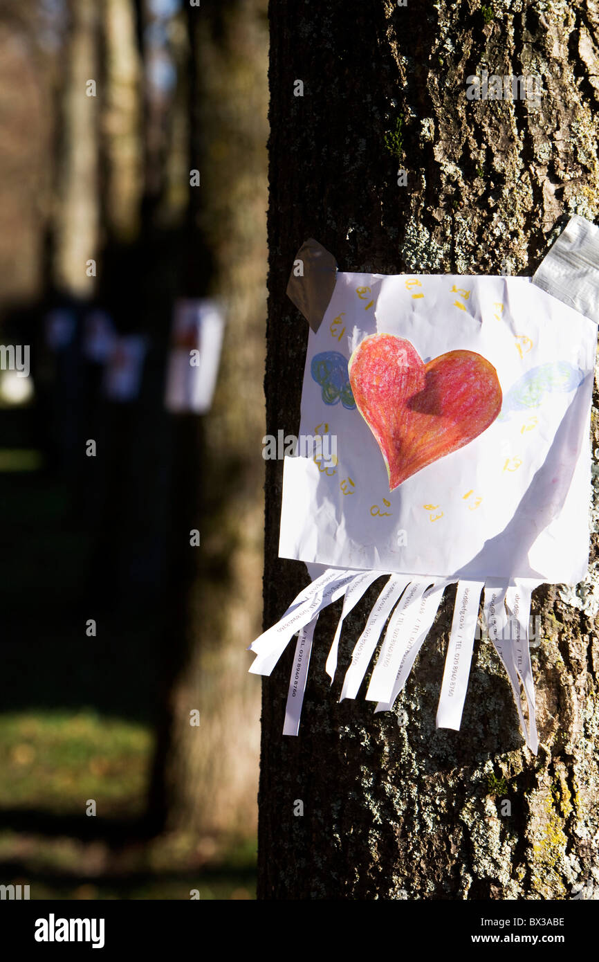 note with red heart sticking on tree - Stock Image