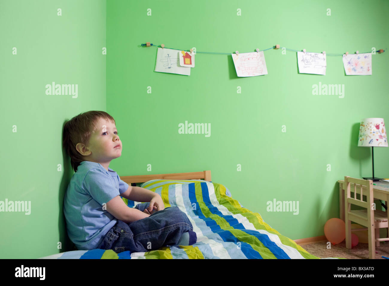 young boy sitting on bed in children´s room - Stock Image