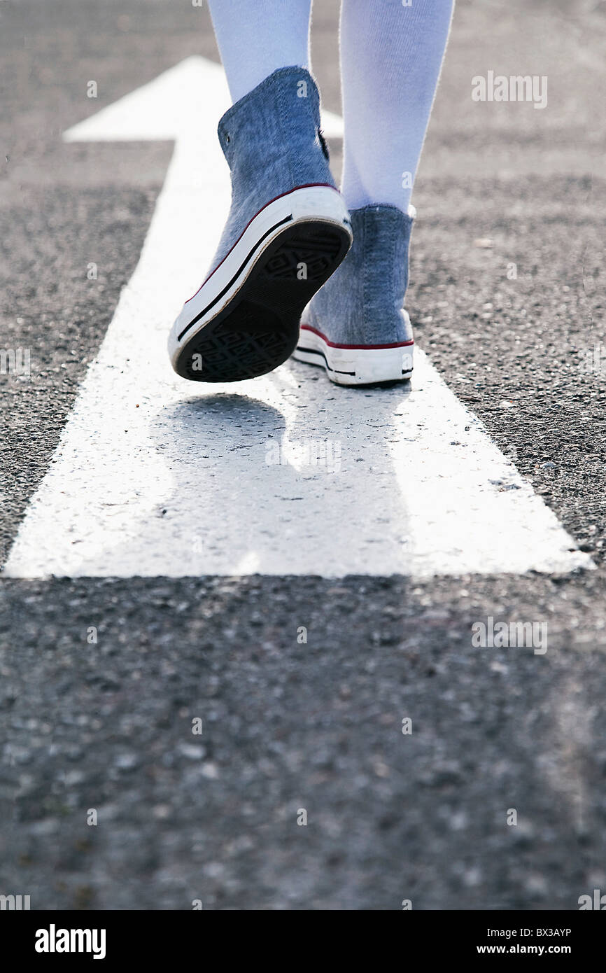 detail of young girl standing on arrow sign on road - Stock Image