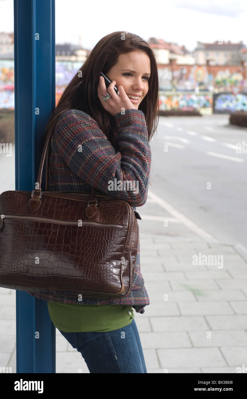 young woman at bus stop talking on mobile phone - Stock Image