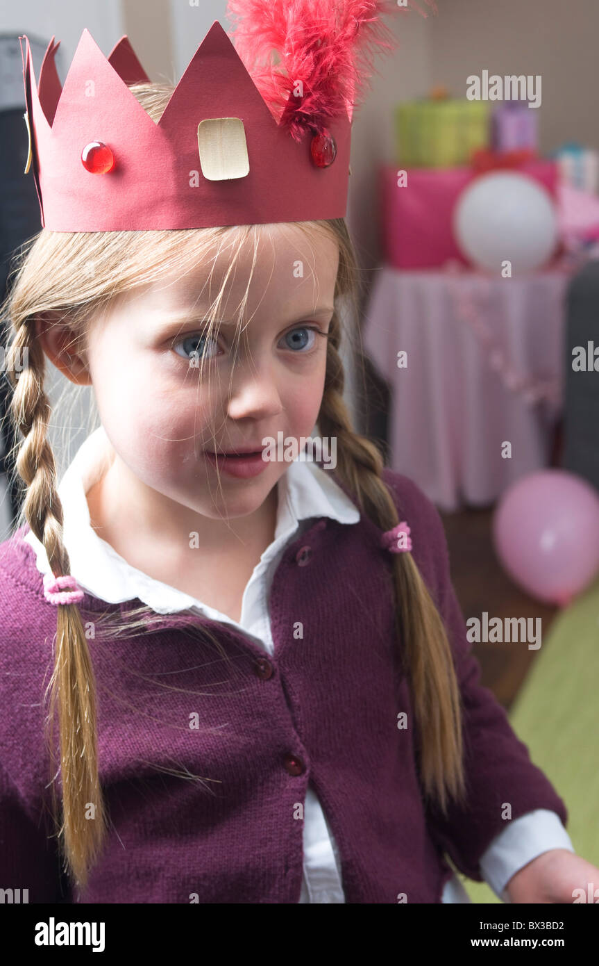 portrait of young girl wearing paper crown at birthday party - Stock Image