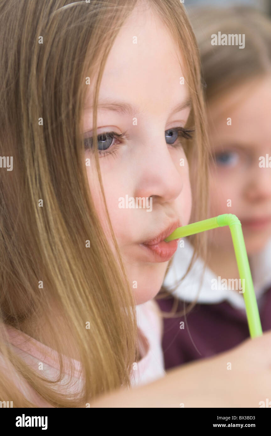 portrait of young girl drinking with straw - Stock Image