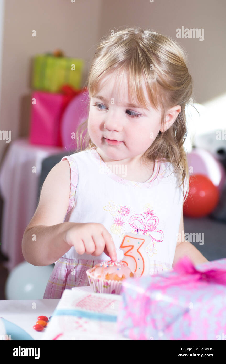 portrait of young girl with cupcake at birthday party - Stock Image