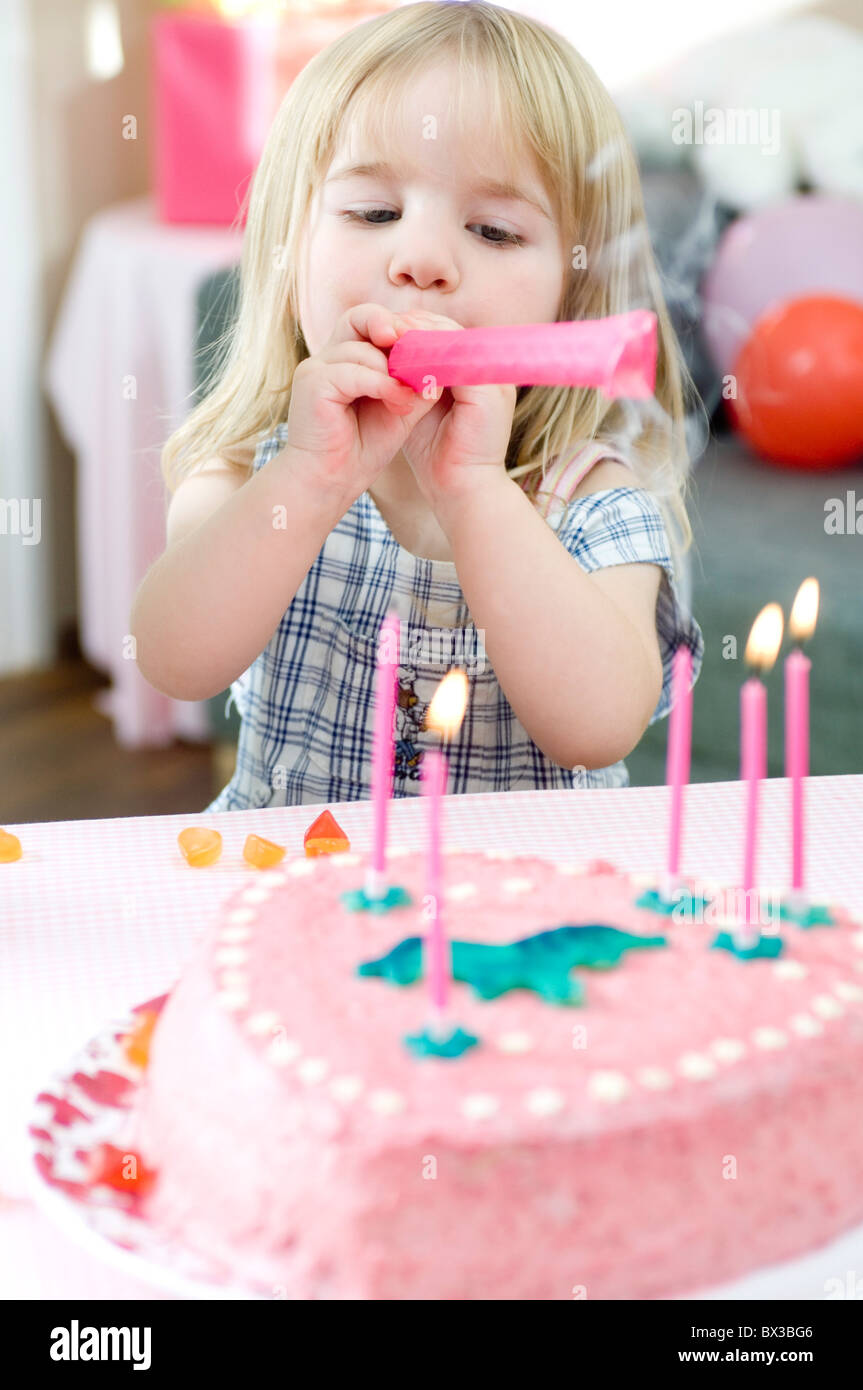 portrait of young girl blowing out candles on birthday cake - Stock Image