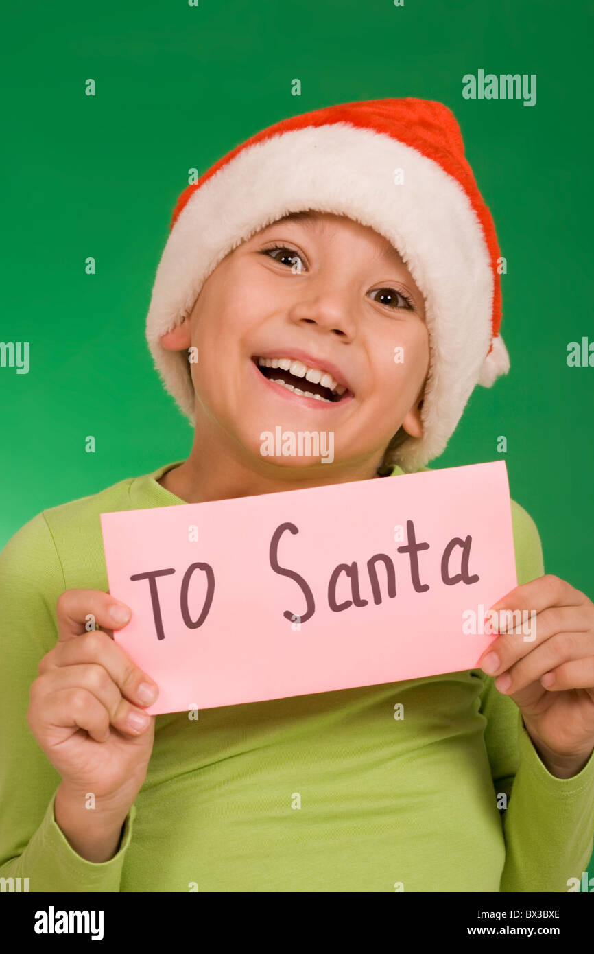 Happy lad holding letter with note 'To Santa' over green background - Stock Image
