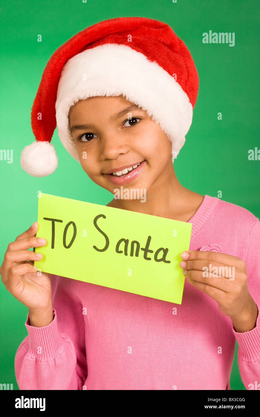 Happy girl holding letter with note 'To Santa' over green background - Stock Image