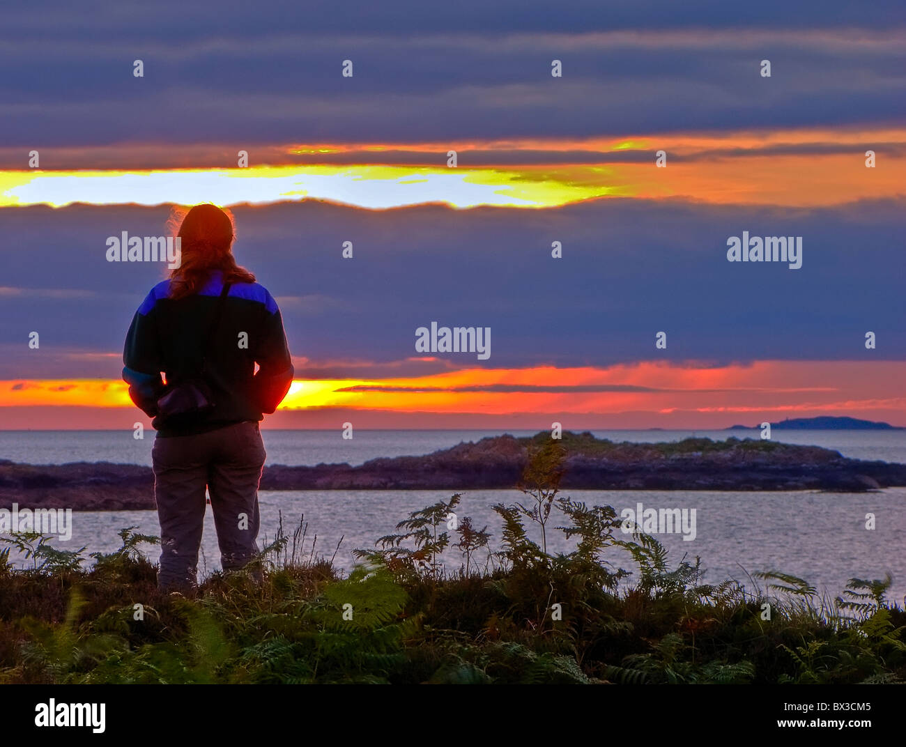 Girl teen or twenties looking towards sunrise or sunset perhaps contemplating her past, future or relationship. - Stock Image