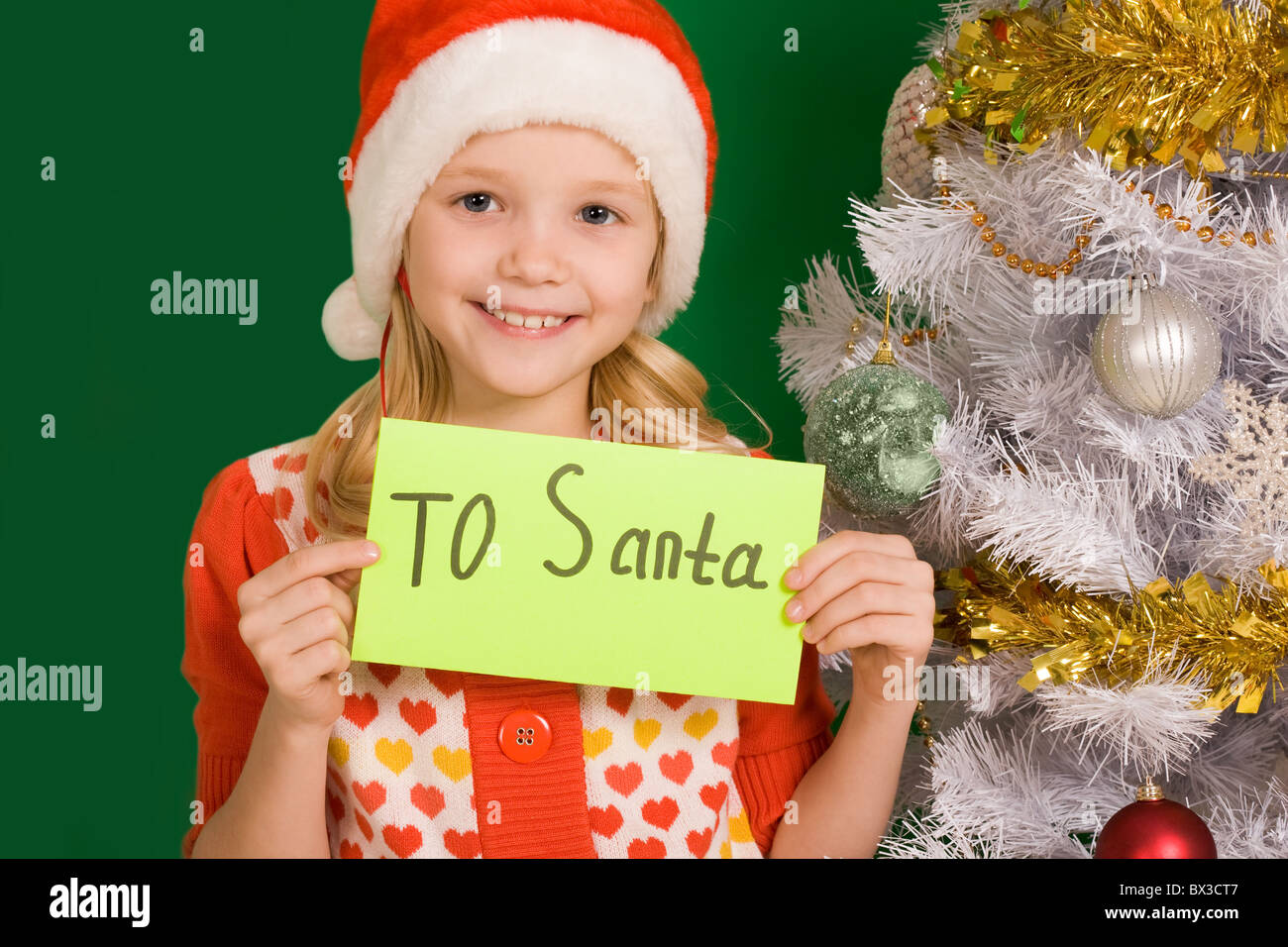 Happy girl holding letter with note 'To Santa' with decorated firtree near by - Stock Image