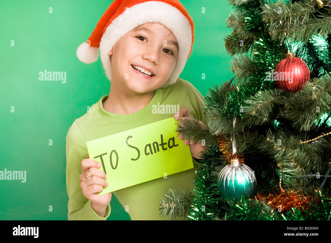 Happy lad holding letter with note 'To Santa' with decorated firtree near by - Stock Image