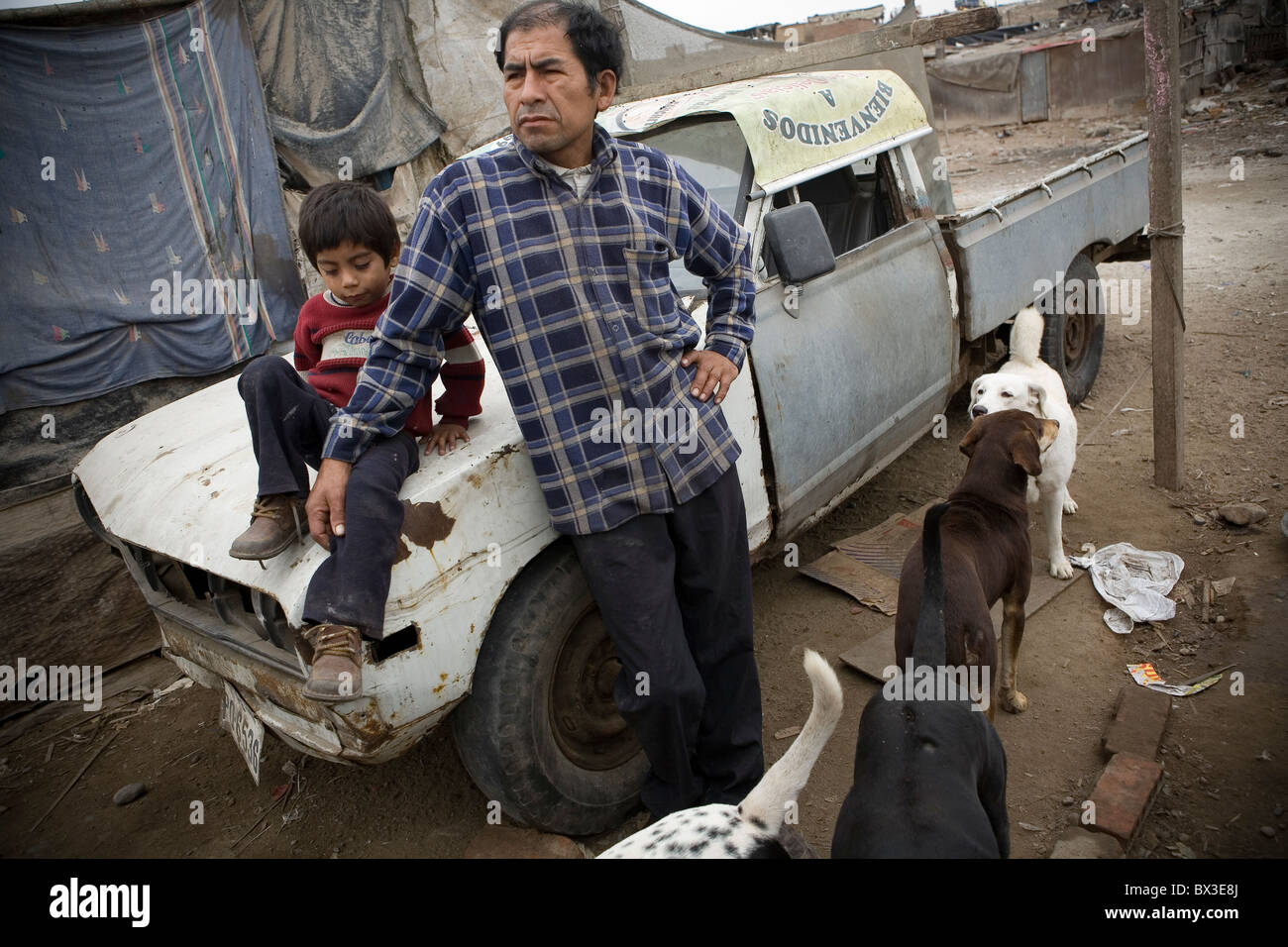 Man and his child with a truck outside their house. Villa el Salvador, Lima, Peru. - Stock Image
