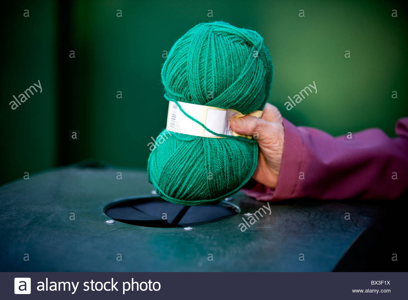 A senior woman recycling a ball of wool Stock Photo