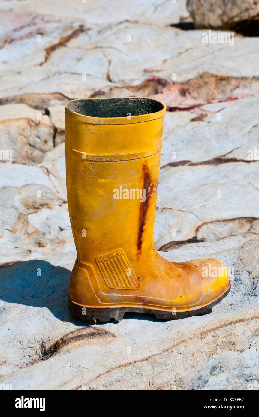 An old yellow wellington boot washed up on a rocky beach - Stock Image