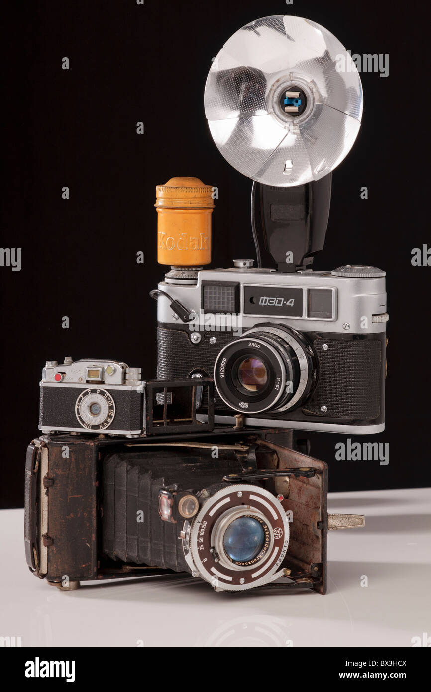 Old camera collection comprising of 1 folding camera 1 Russian copy of a Leica and 1 miniature KKW lighter shaped - Stock Image