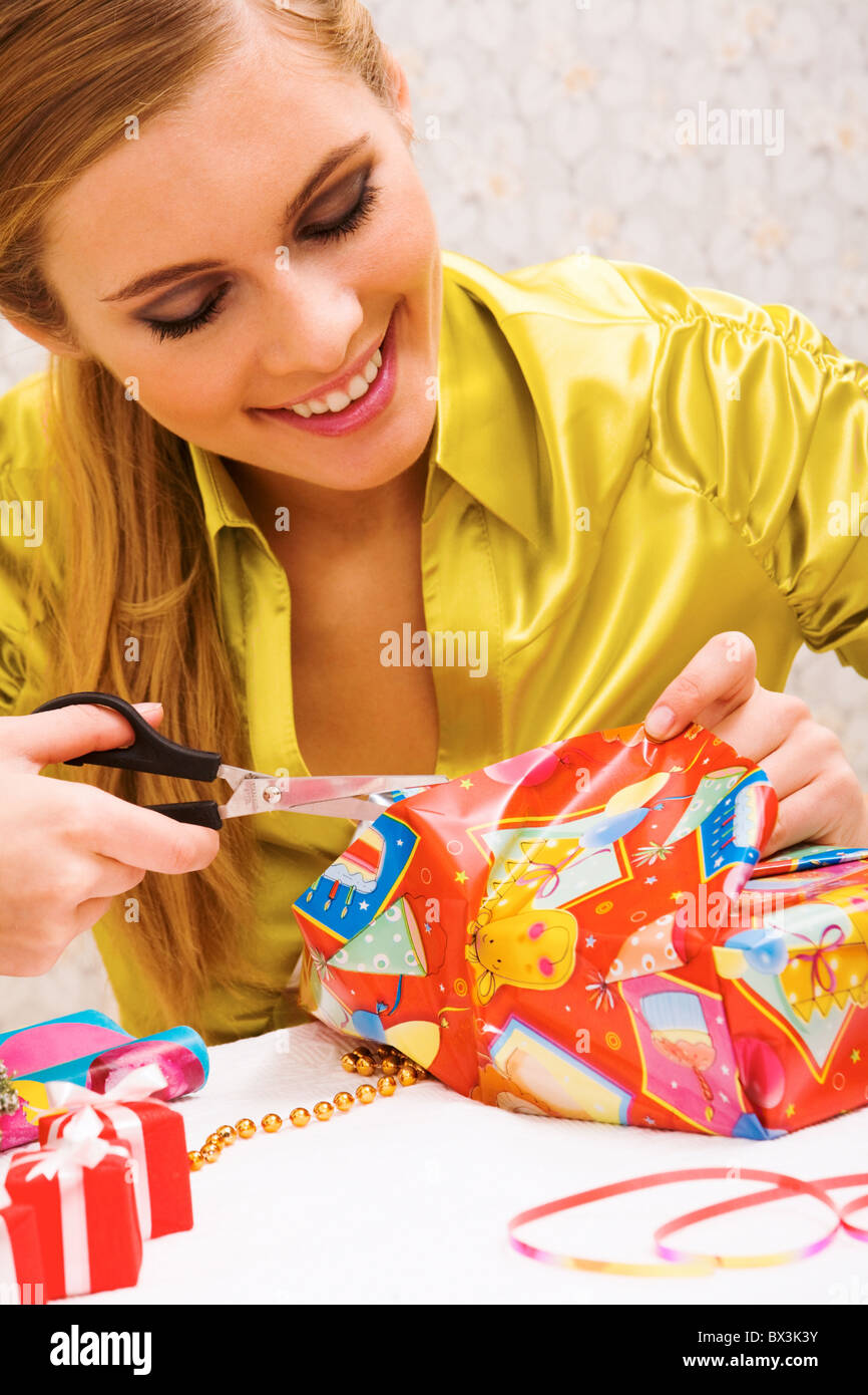 Happy woman wrapping Christmas presents before holiday Stock Photo