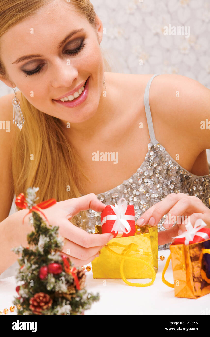 Portrait of happy girl putting small giftbox into golden package Stock Photo