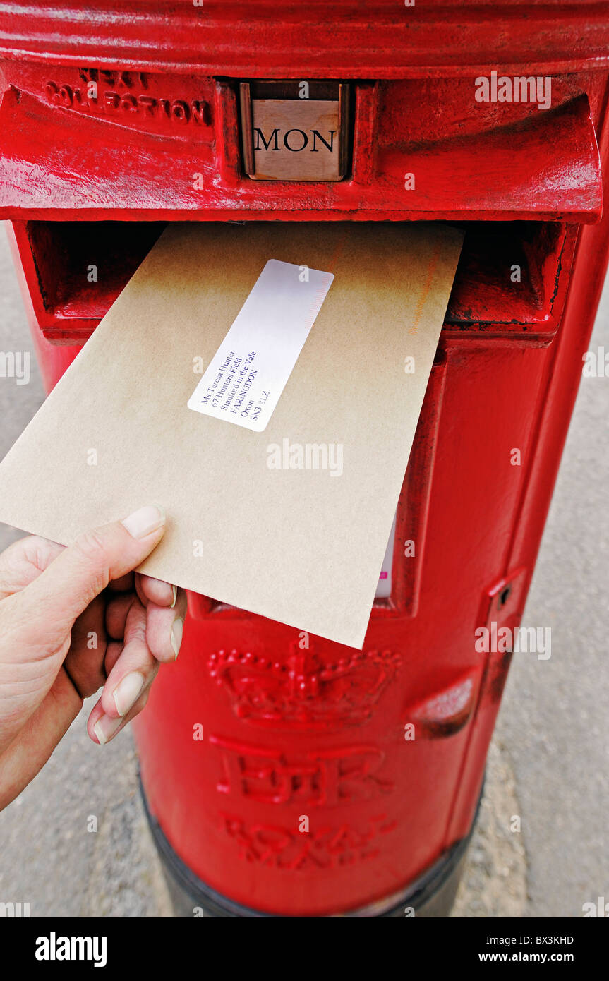 Posting a Letter Into a Post Box, UK. - Stock Image