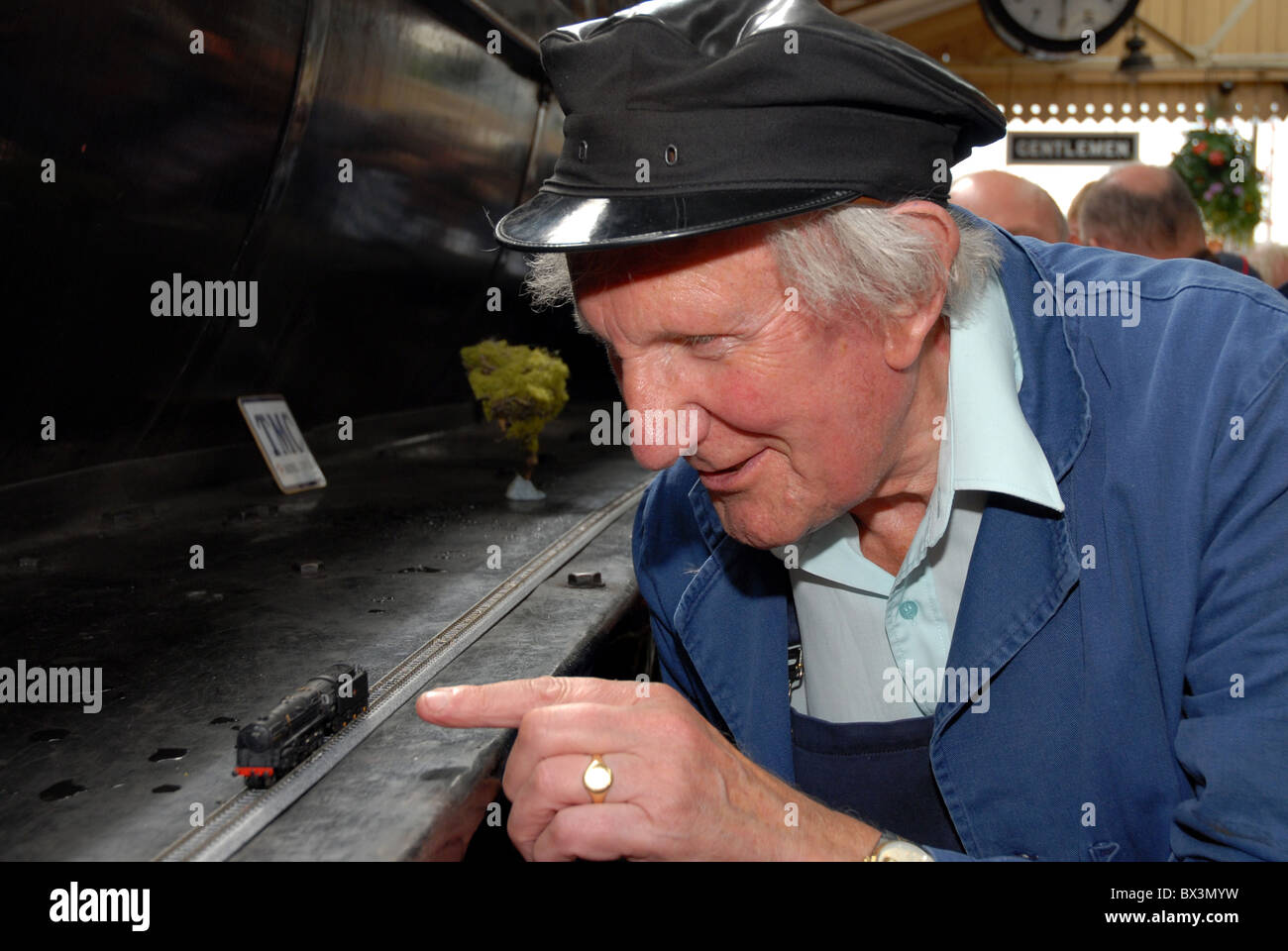 Famous Wildlife and railway artist David Shepherd inspects a N gauge model of his own locomotive no. - Stock Image