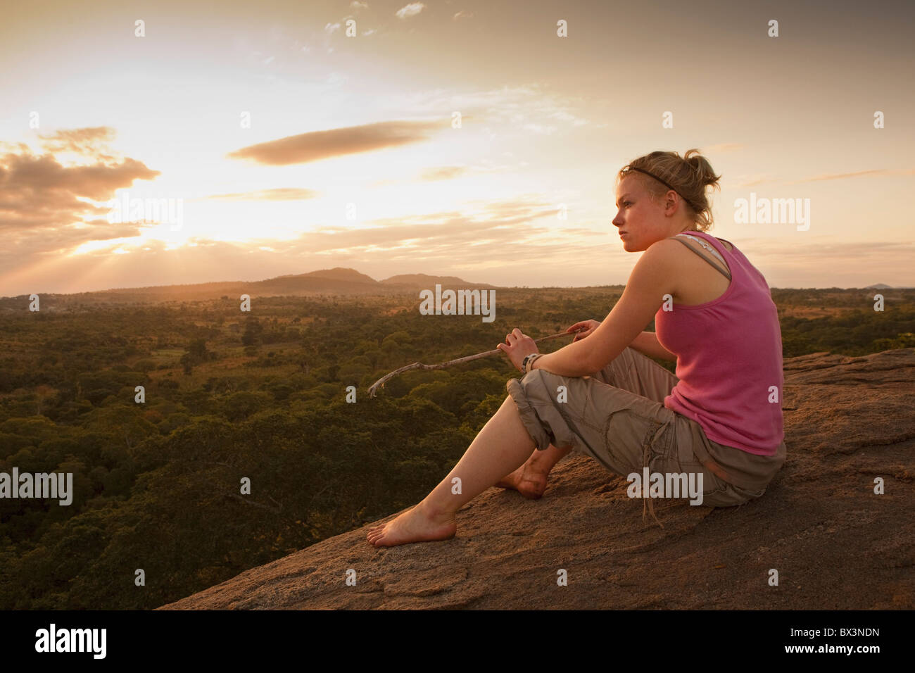 A Young Woman Looking Over The African Landscape; Manica, Mozambique, Africa - Stock Image