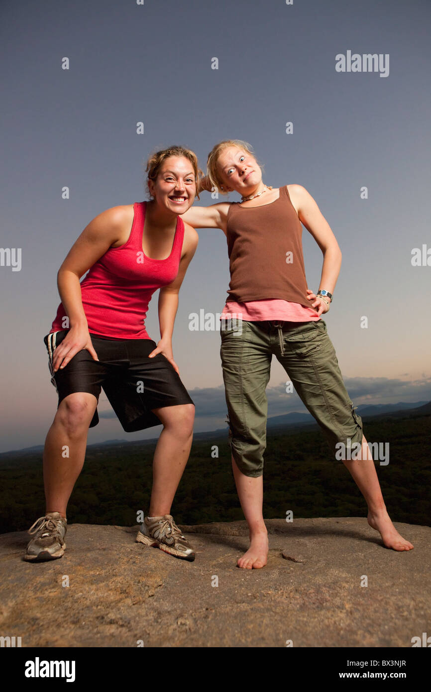 Two Young Women Doing Silly Poses On A Rock; Manica, Mozambique, Africa - Stock Image