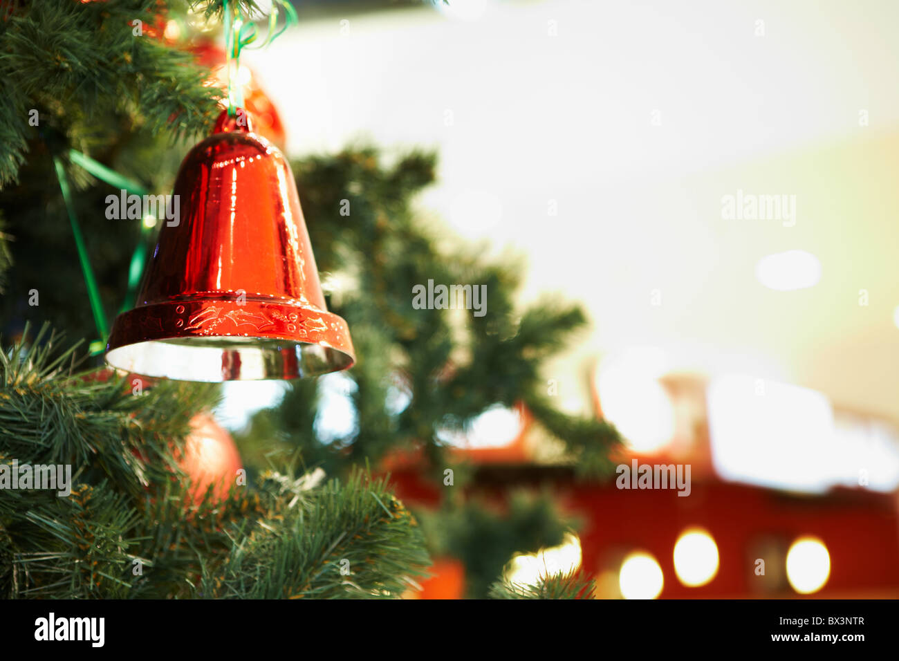 Close-up of red toy bell hanging on green spruce branch - Stock Image