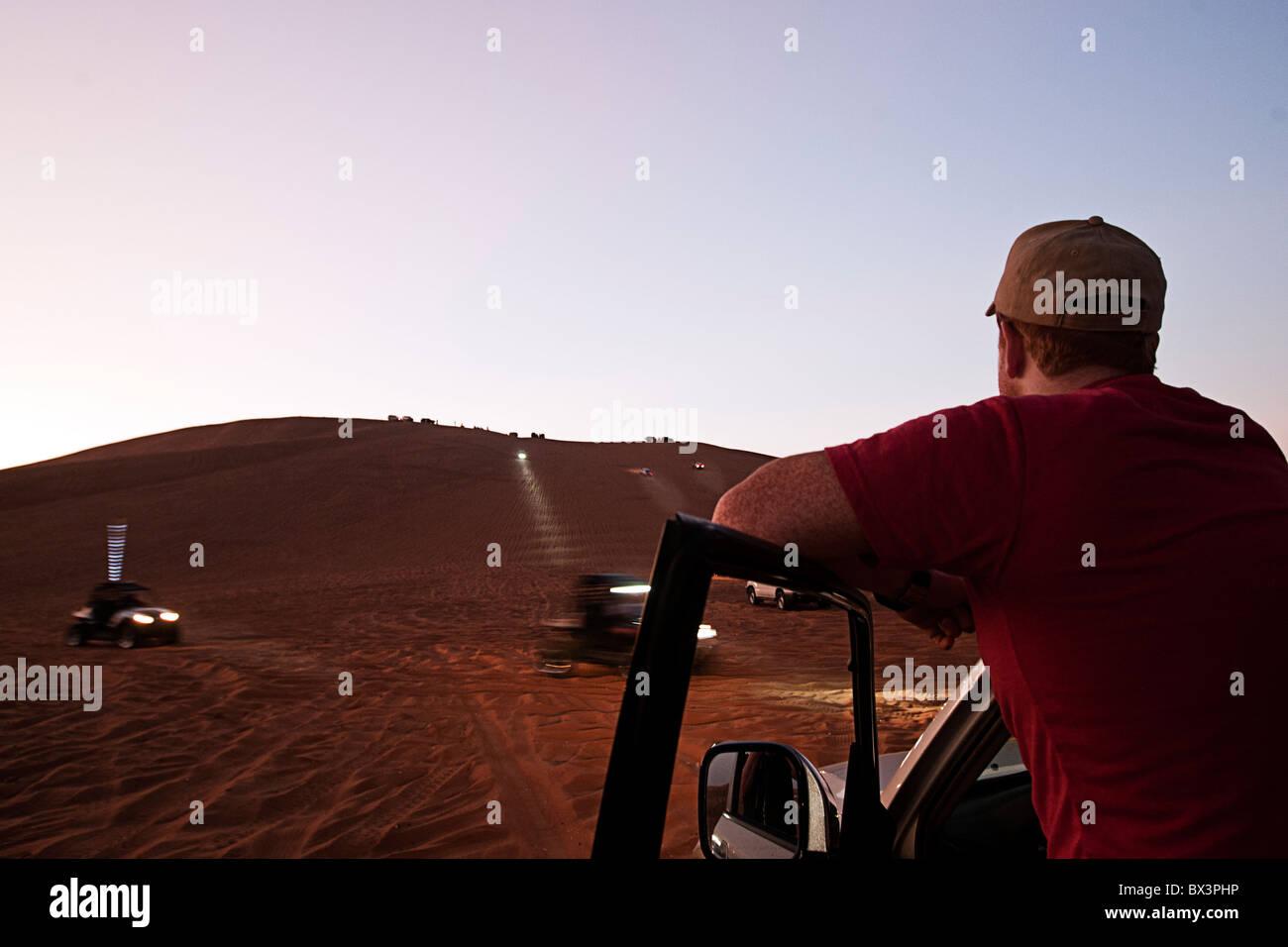 Man watching 4x4s on the Big Red sand dune in Dubai, UAE - Stock Image