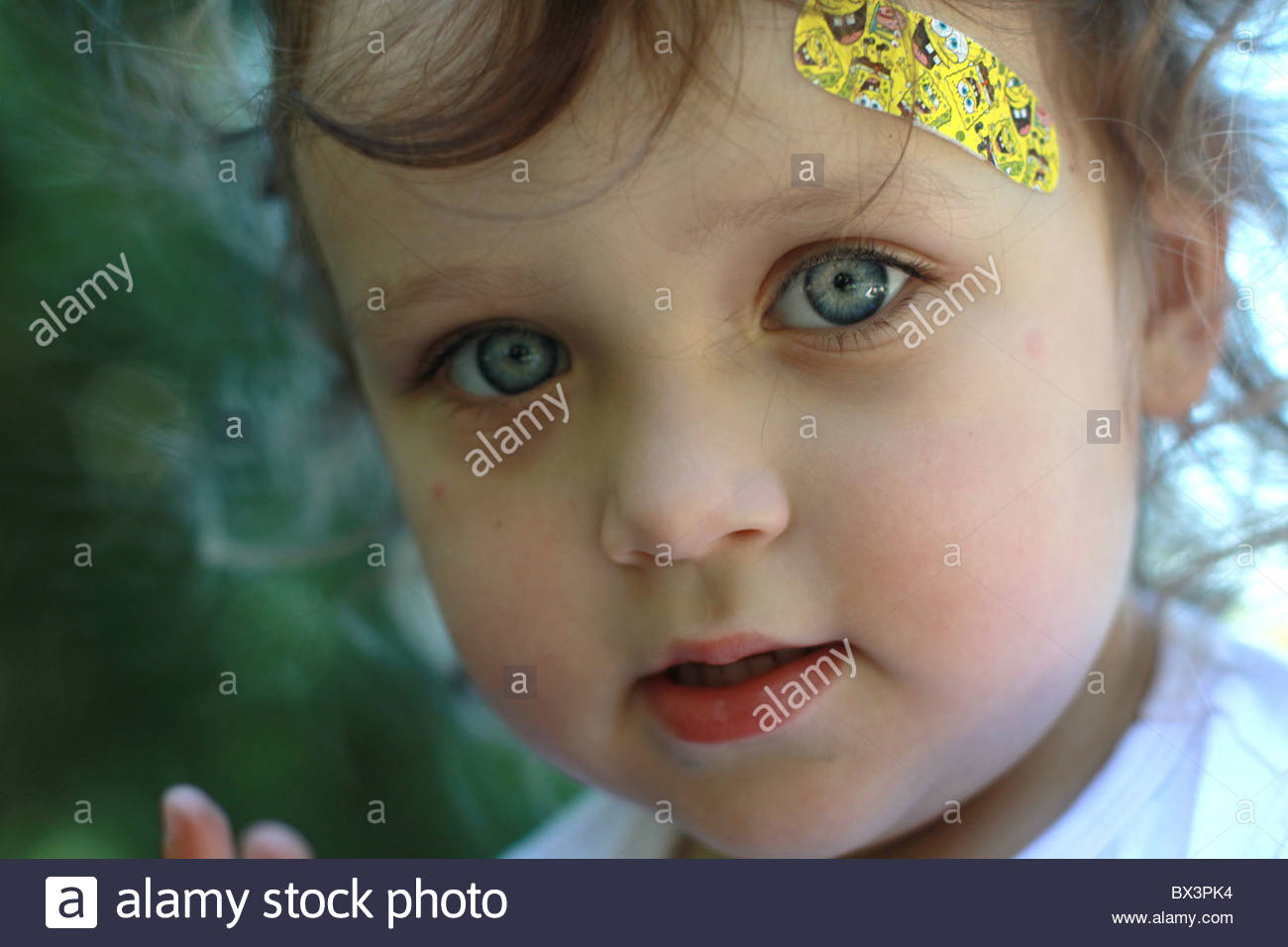 A Close Up Of A Two Year Old Girl With A Bandaid On Her Head Stock