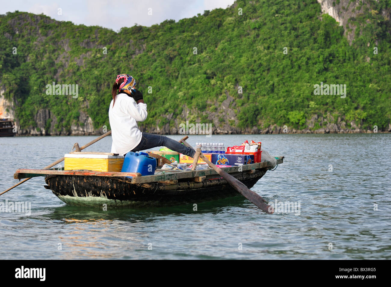 Unidentified woman talks in her mobil phone while rowing her boat.  Mobile coverage is obviously good also far away - Stock Image