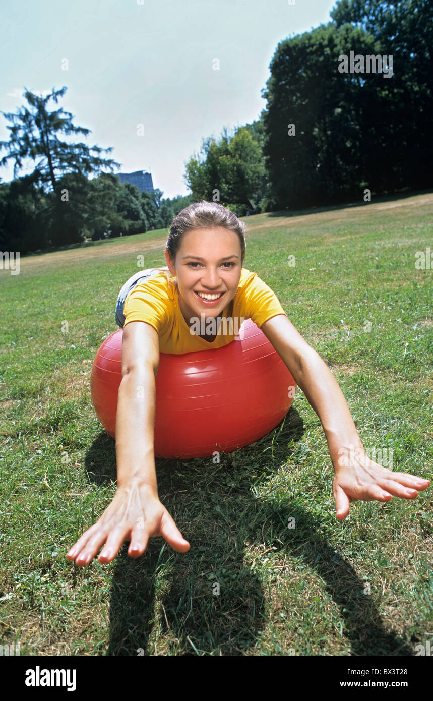 Girl exercising on the meadow in the summer - Stock Image