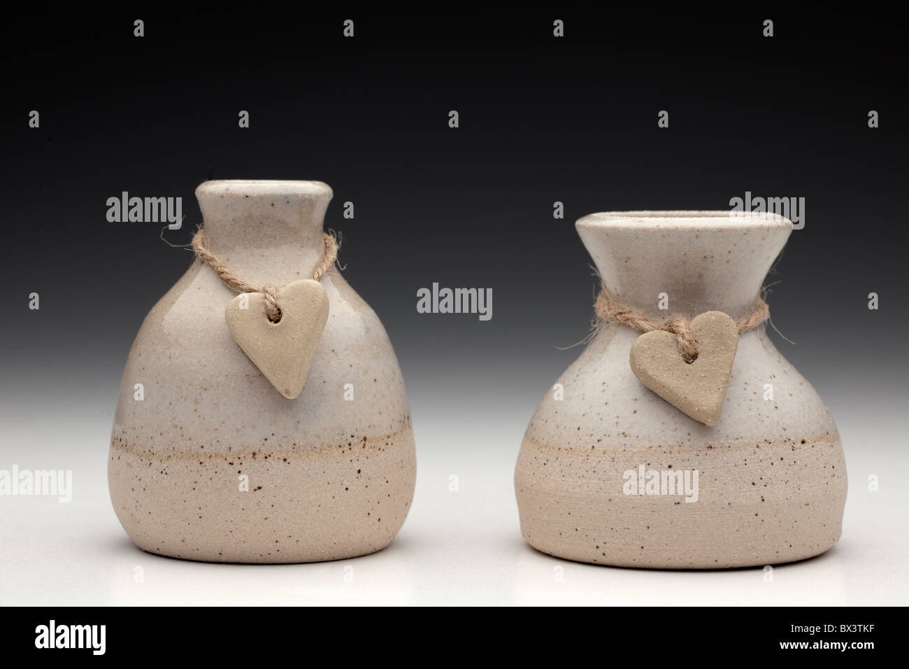 Two stone hearts on string wrapped around two ceramic pots - Stock Image