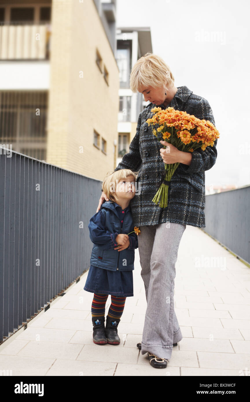 Woman with a little girl standing outdoors. - Stock Image