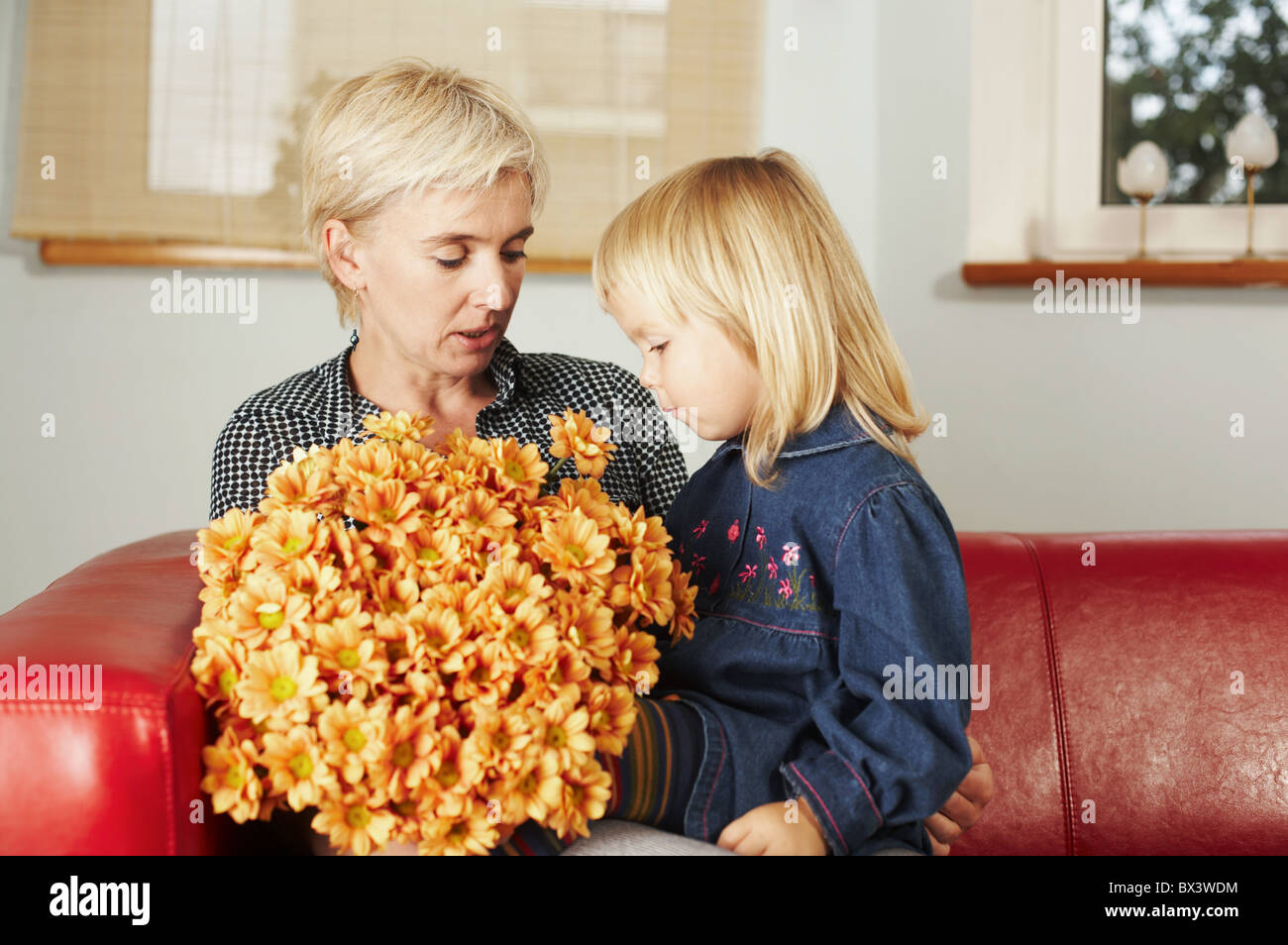 Mother with a little girl holding bench of flowers. - Stock Image