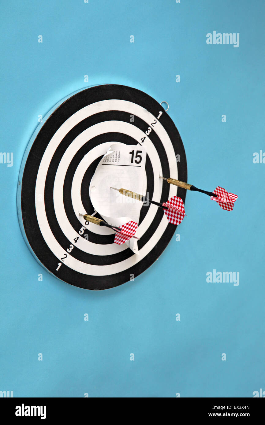 dart board with dart holding calendar page April 15th tax day in bullseye - Stock Image