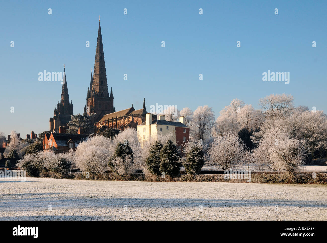 Lichfield Cathedral spires seen fro Stowe Fields under snow with hoar frost on trees and winter snow on ground under - Stock Image