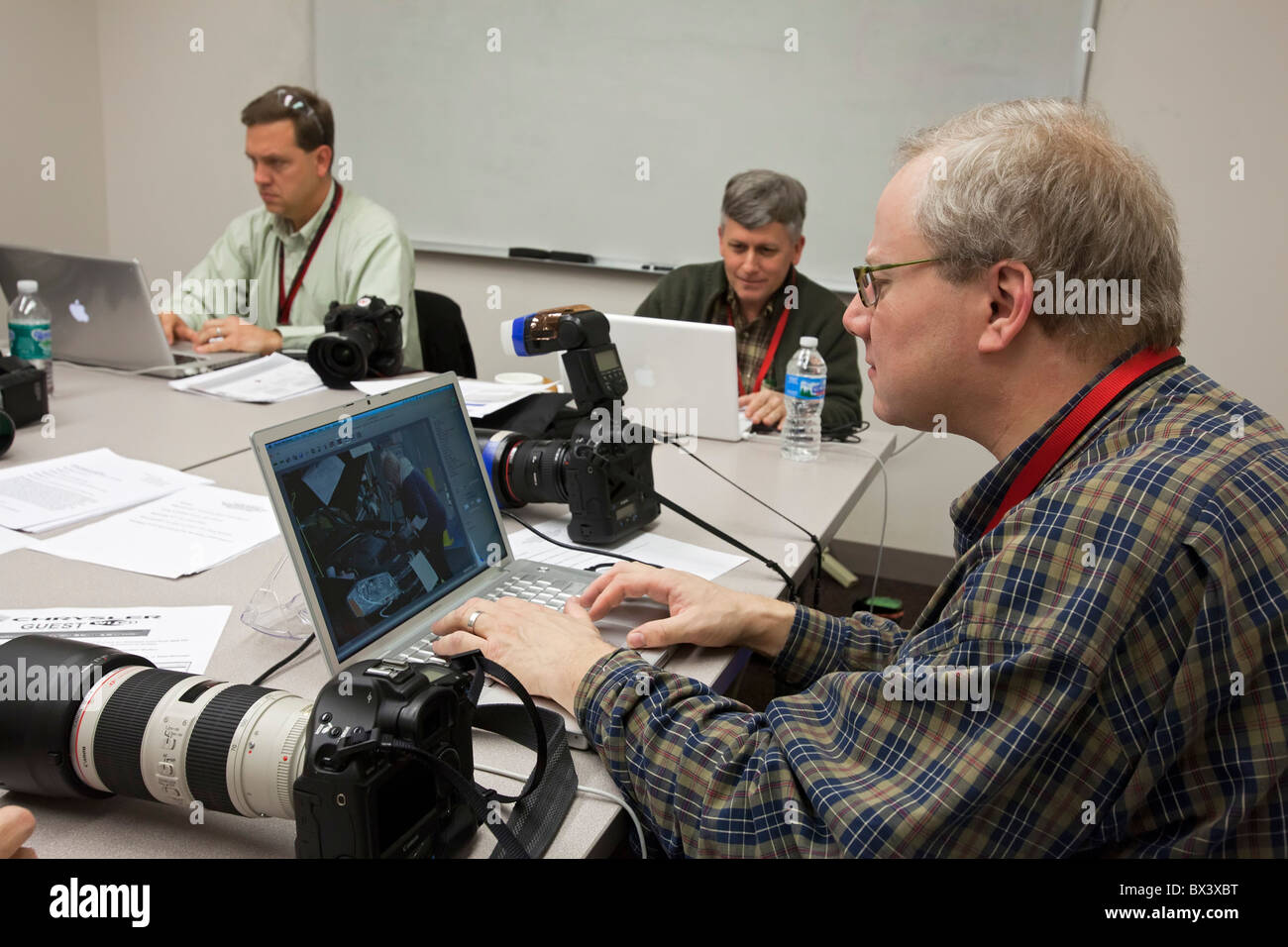 News Photographers Edit and File Pictures - Stock Image
