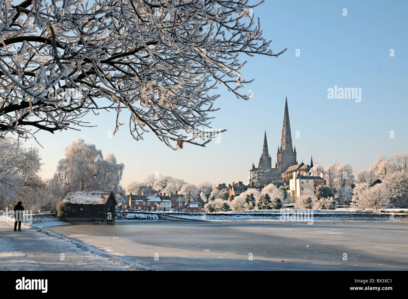 Lichfield Cathedral from Stowe Pool with boat house and tree in winter snow ice and sunshine and hoar frost and - Stock Image