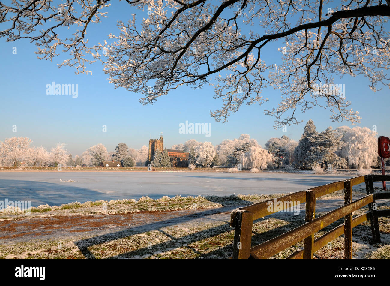 St Saint Chad Chad's Church Lichfield with frozen Stowe Pool in winter sunshine - Stock Image