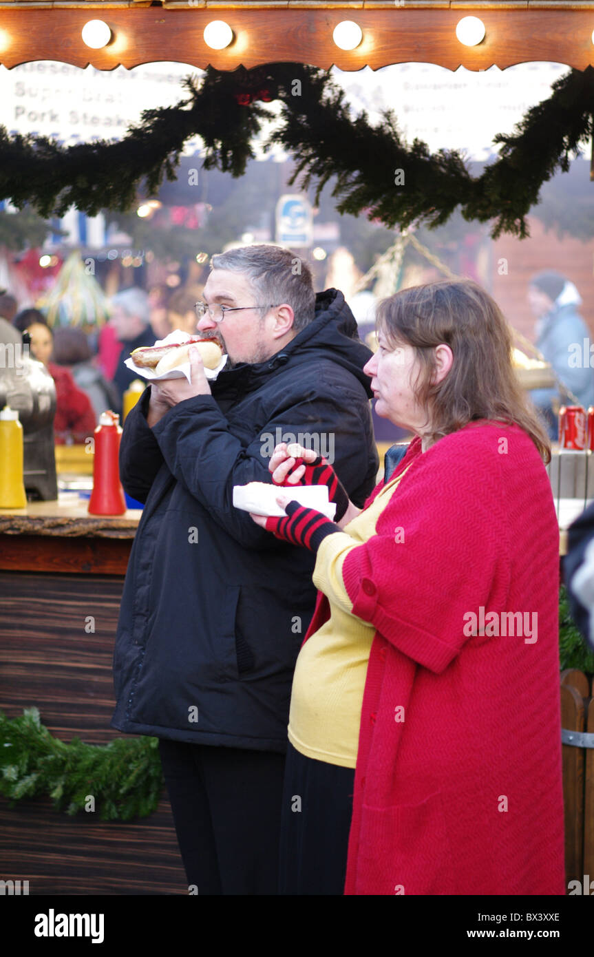 Fat people eating junk food in Manchester Christmas market - Stock Image