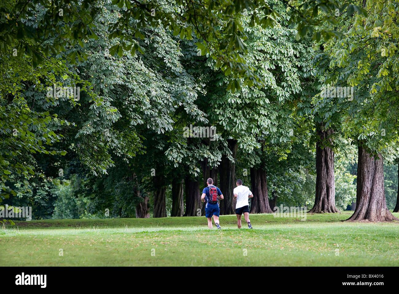 Two men running in park Northampton UK - Stock Image