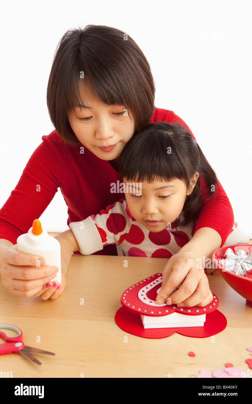 A Mother And Daughter Making A Valentine's Day Craft - Stock Image