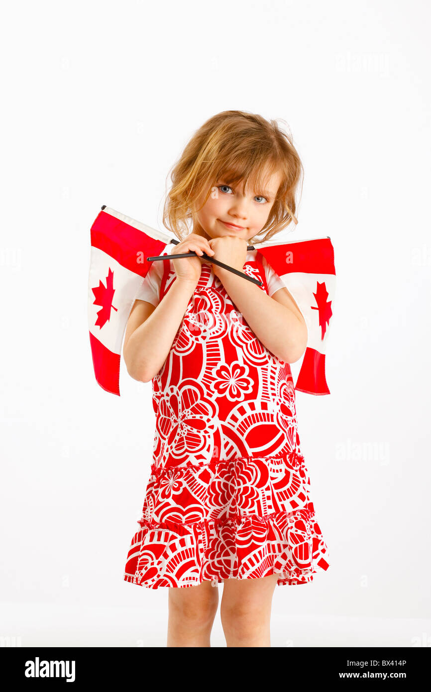 A Girl Holding Two Canada Flags - Stock Image